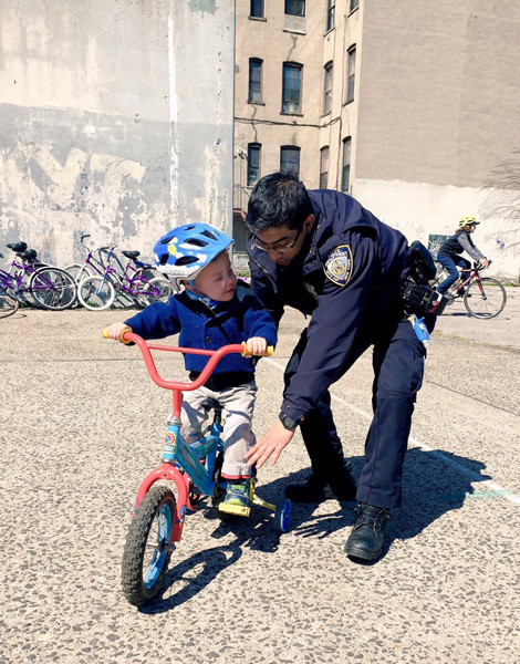 "Joanna Smith ""First Time on Two (Four) Wheels"" (Brooklyn, USA) ""I helped organize a day to celebrate all things kids and bikes in Bed-Stuy this Spring. It was this tiny (brave!) kid's first time on a bike. He got an assist from an officer from the local precinct which was pretty darn cute."""